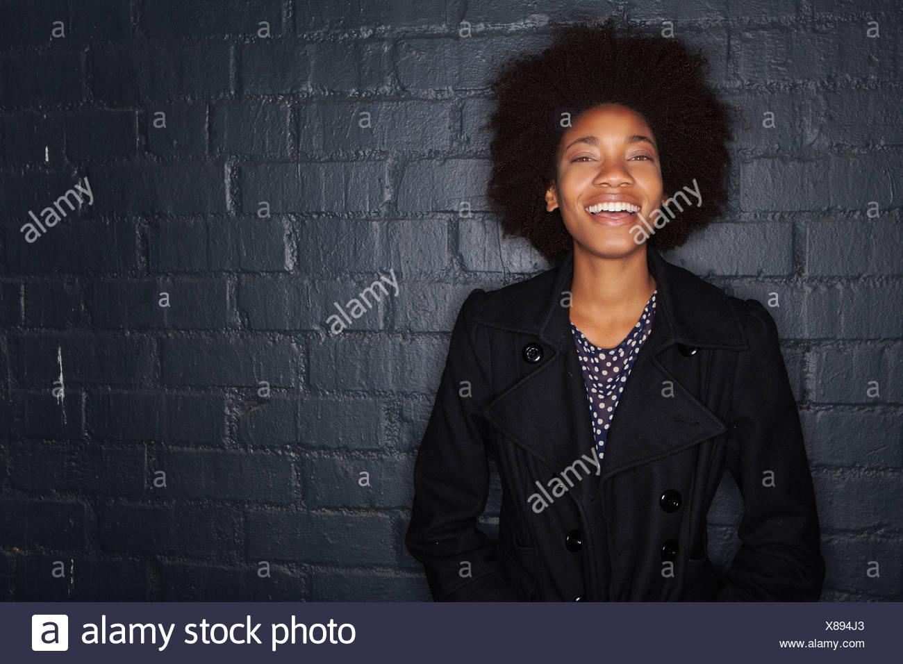 Young woman by black brick wall wearing black jacket - Stock Image