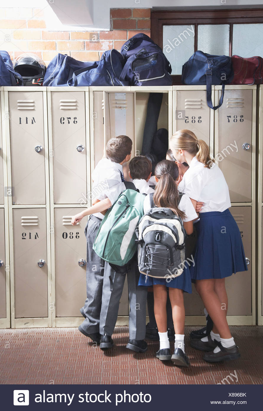 Students in the school hallway looking in a locker - Stock Image