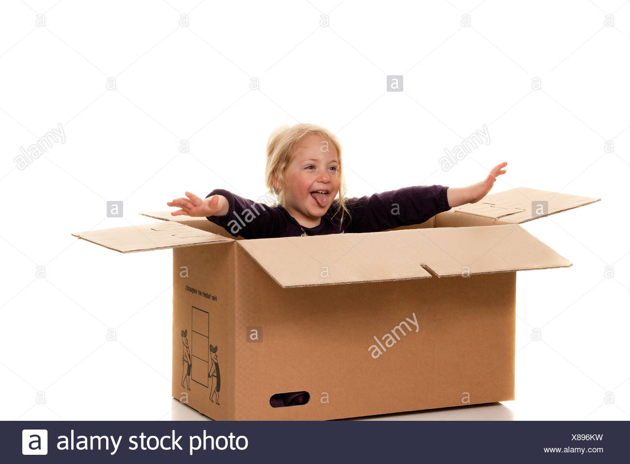 Child in cardboard box. Is moving to box. Stock Photo