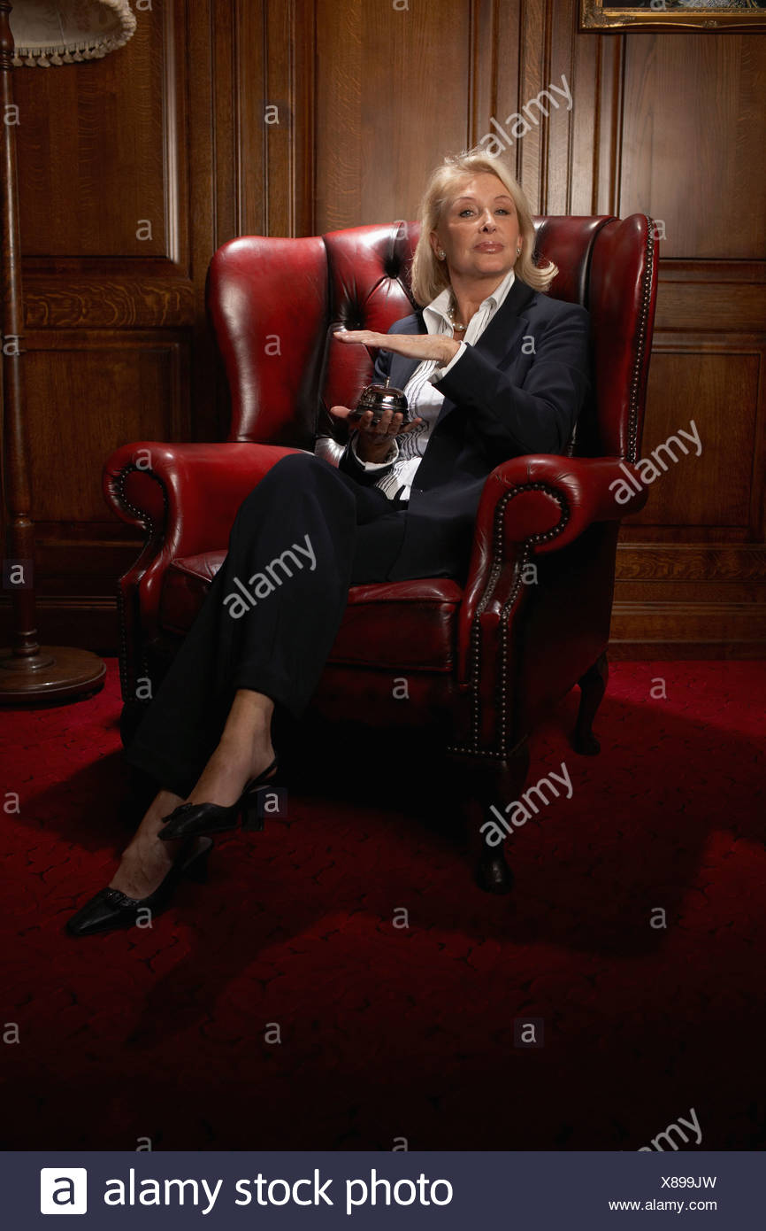 Businesswoman in a comfy leather chair with a candle - Stock Image