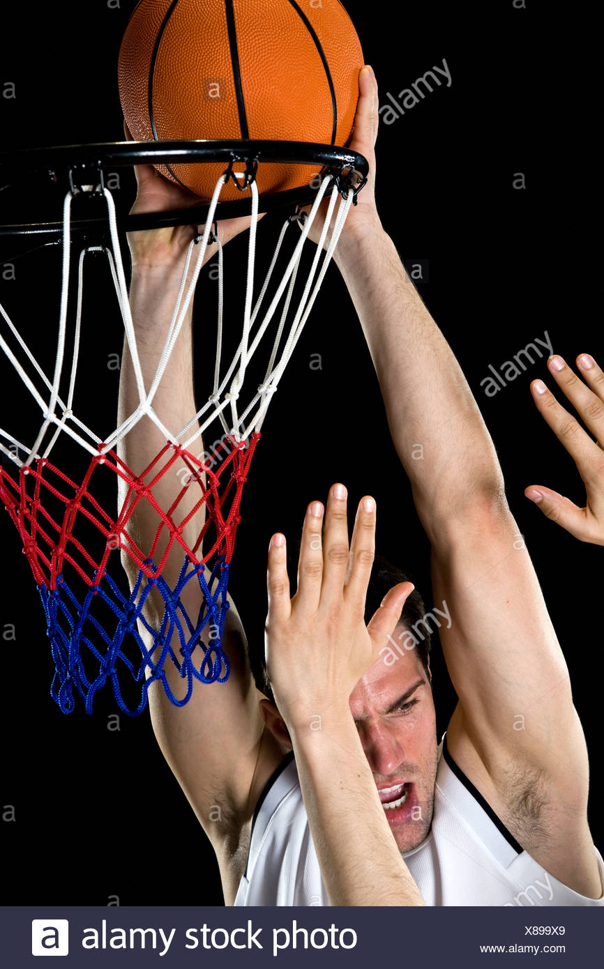 A basketball player trying to make a basket, studio shot Stock Photo