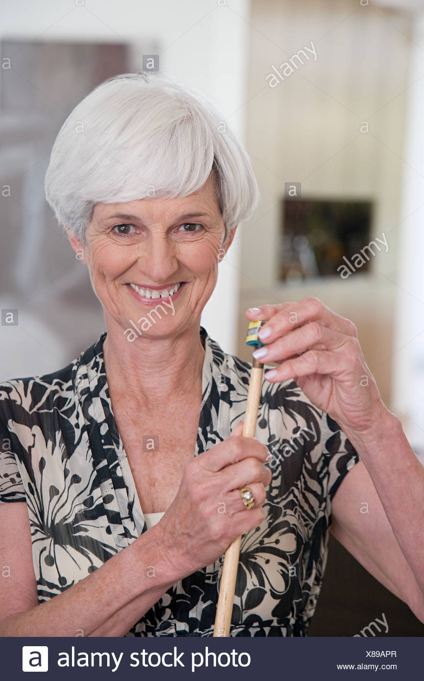 A senior woman holding a snooker cue - Stock Image
