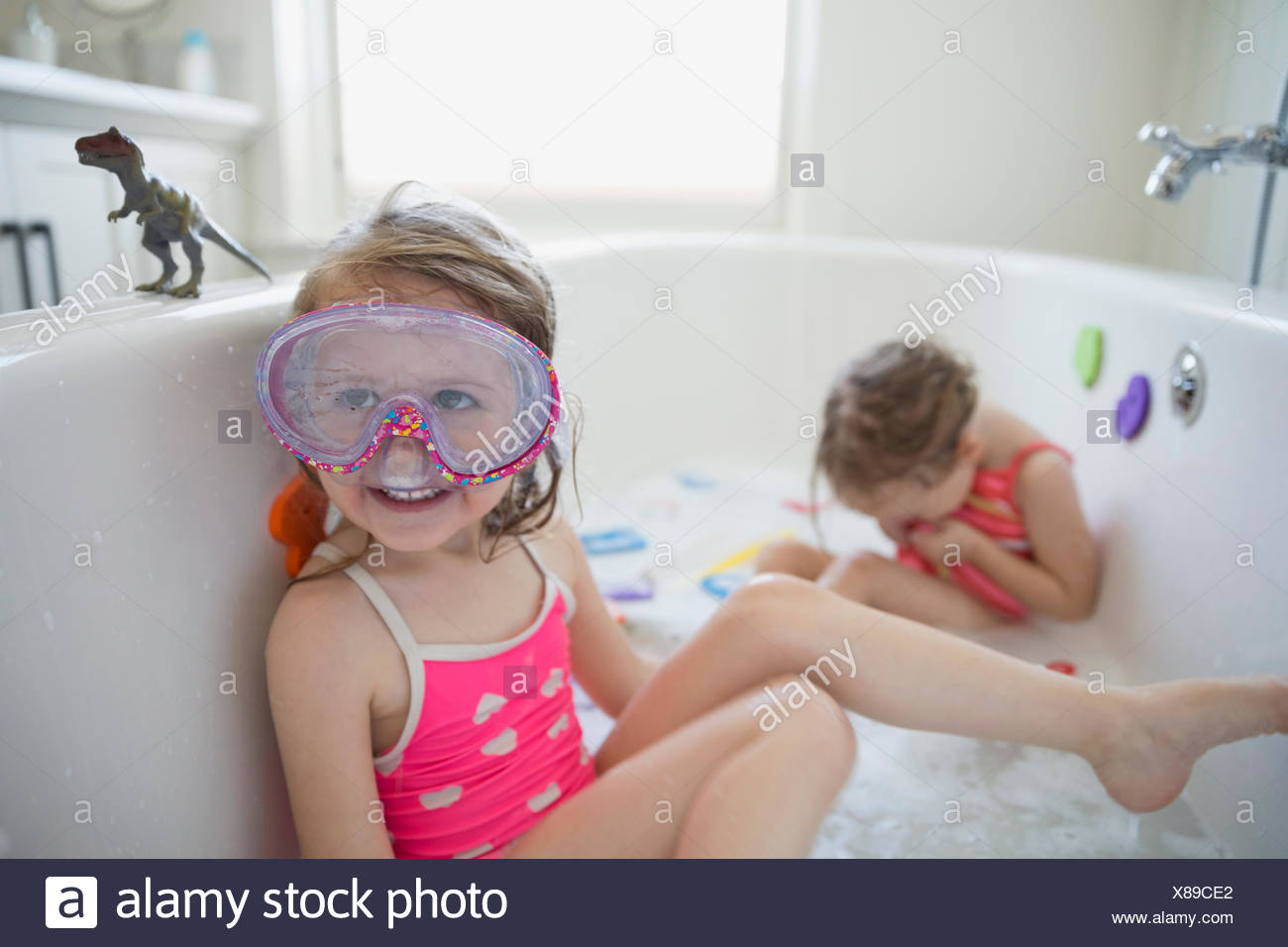 Girl bathing suit and goggles playing bath - Stock Image