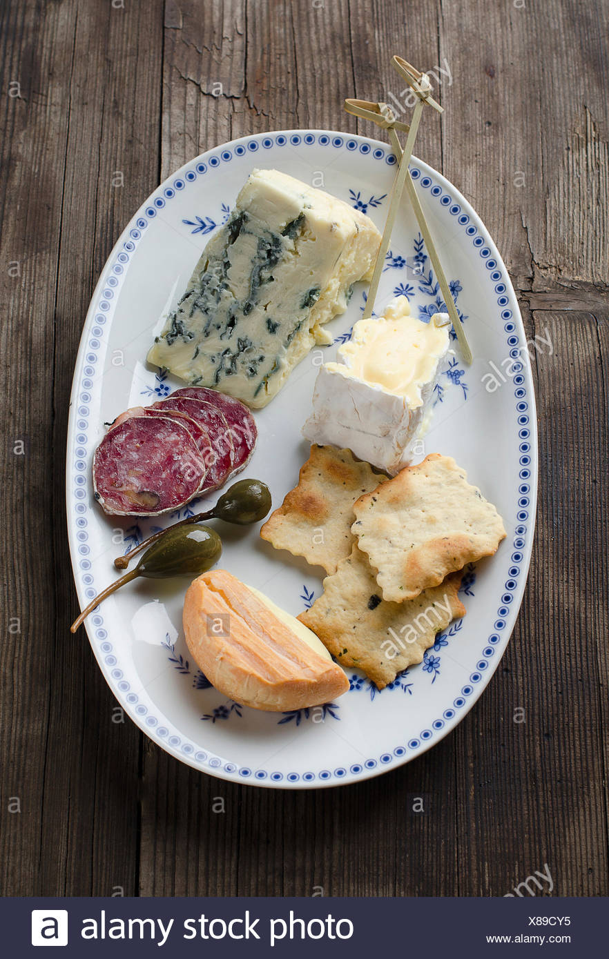 Assortment of fresh cheeses with salami, and crackers - Stock Image