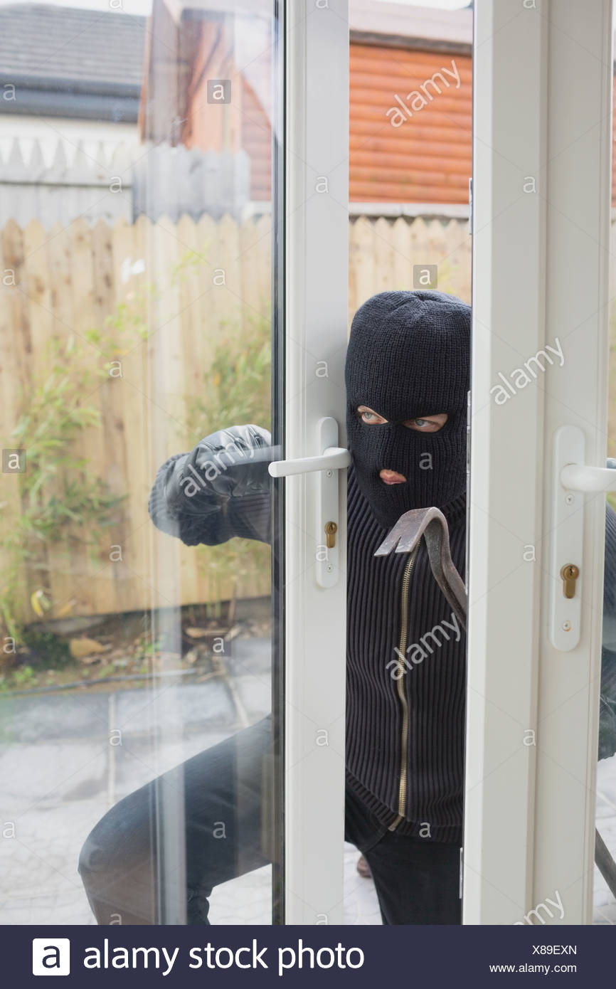 Burglar opening the terrace door - Stock Image : terrace door - pezcame.com
