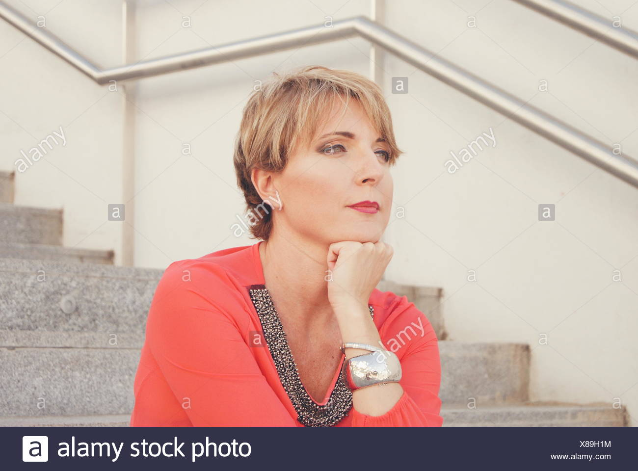Woman sitting on stairs with head on her chin - Stock Image