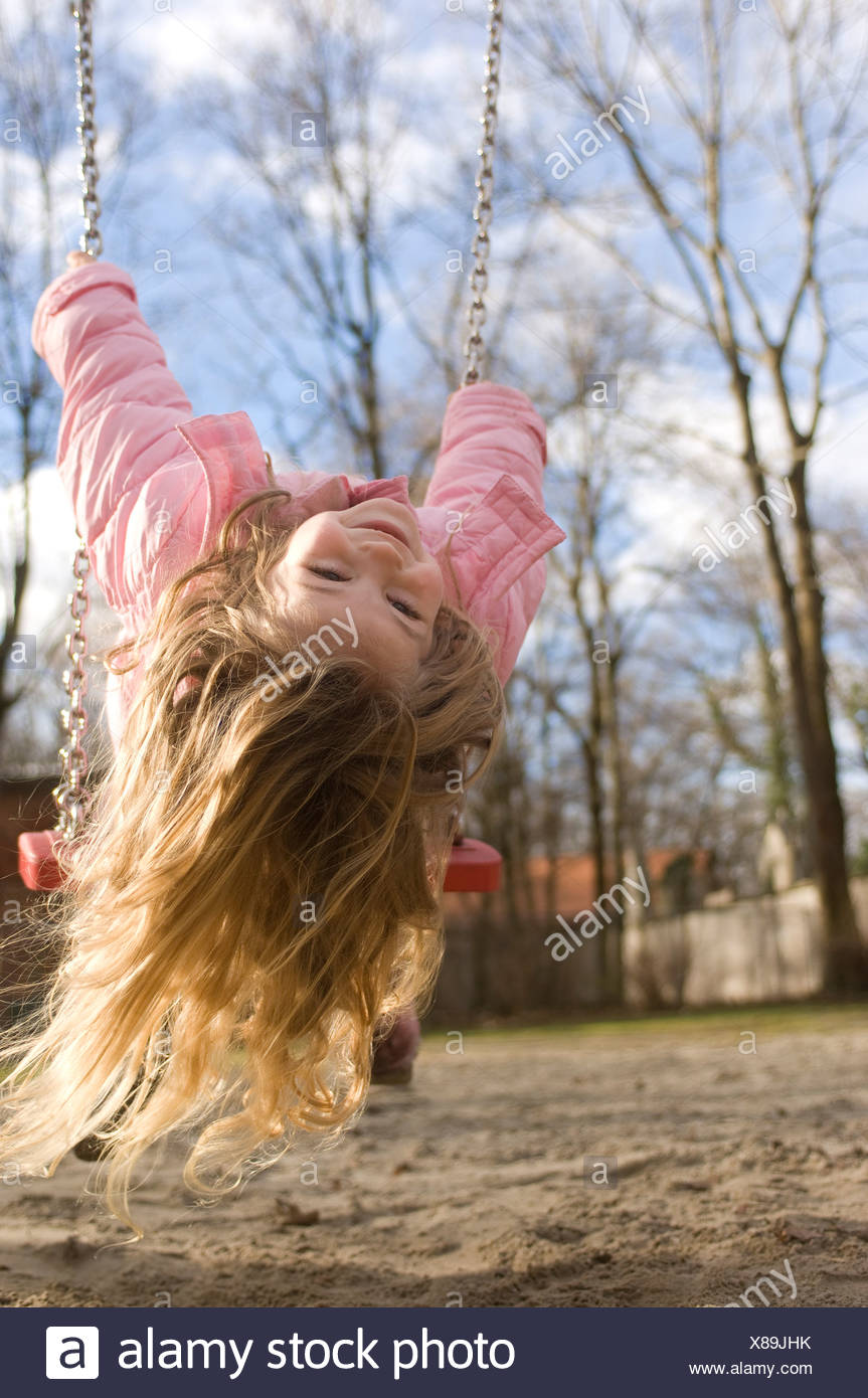 portrait of little girl playing on swing - Stock Image