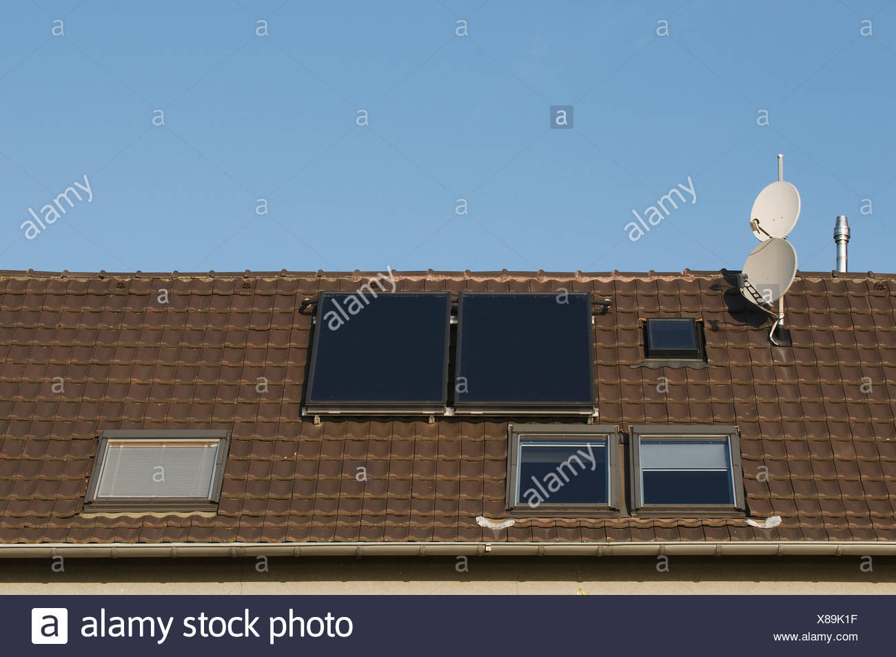 Roof with roof windows, satellite dishes and solar thermal panels, investment in property, PublicGround - Stock Image