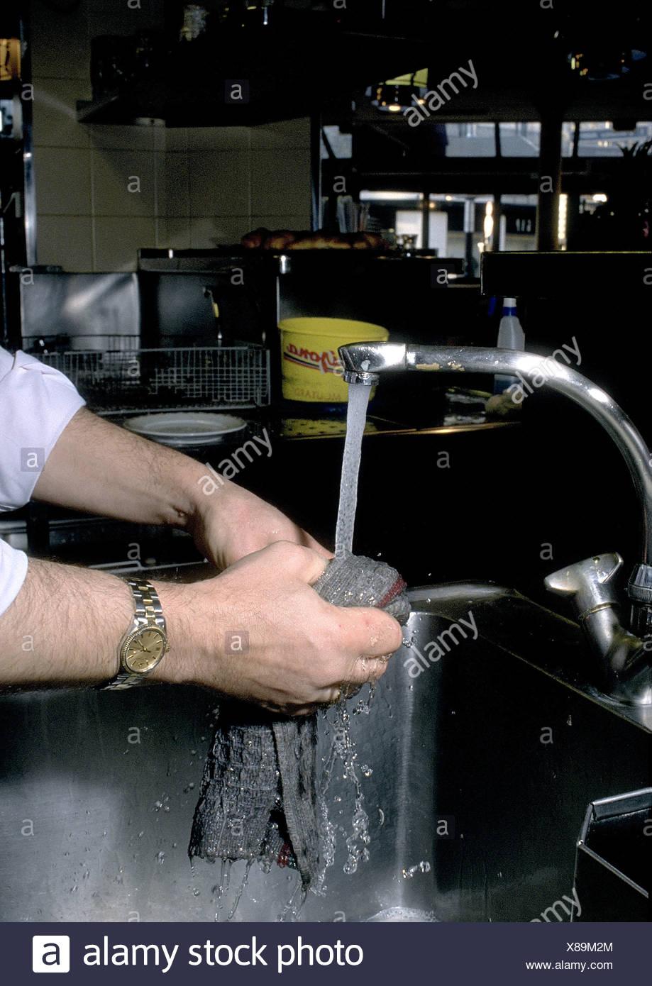 Man washing rag in cafe - Stock Image