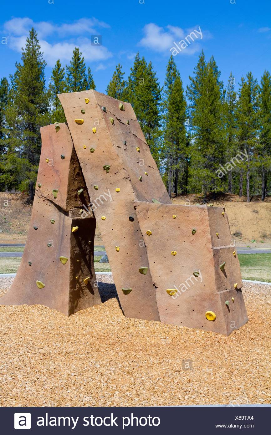 An outdoor rock climbing structure at a playground at a park for kids to practice and play on. - Stock Image