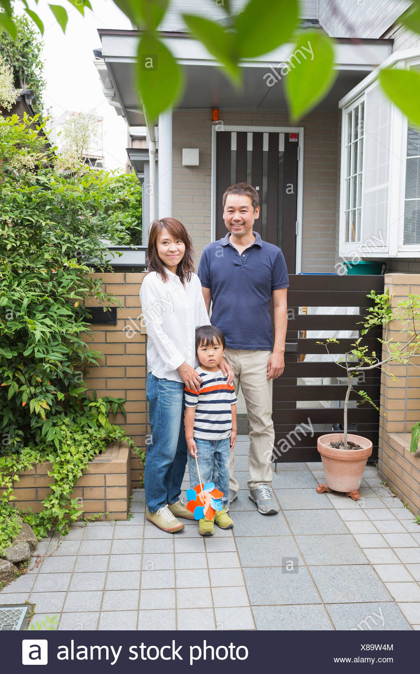 Boy and parents outside home - Stock Image