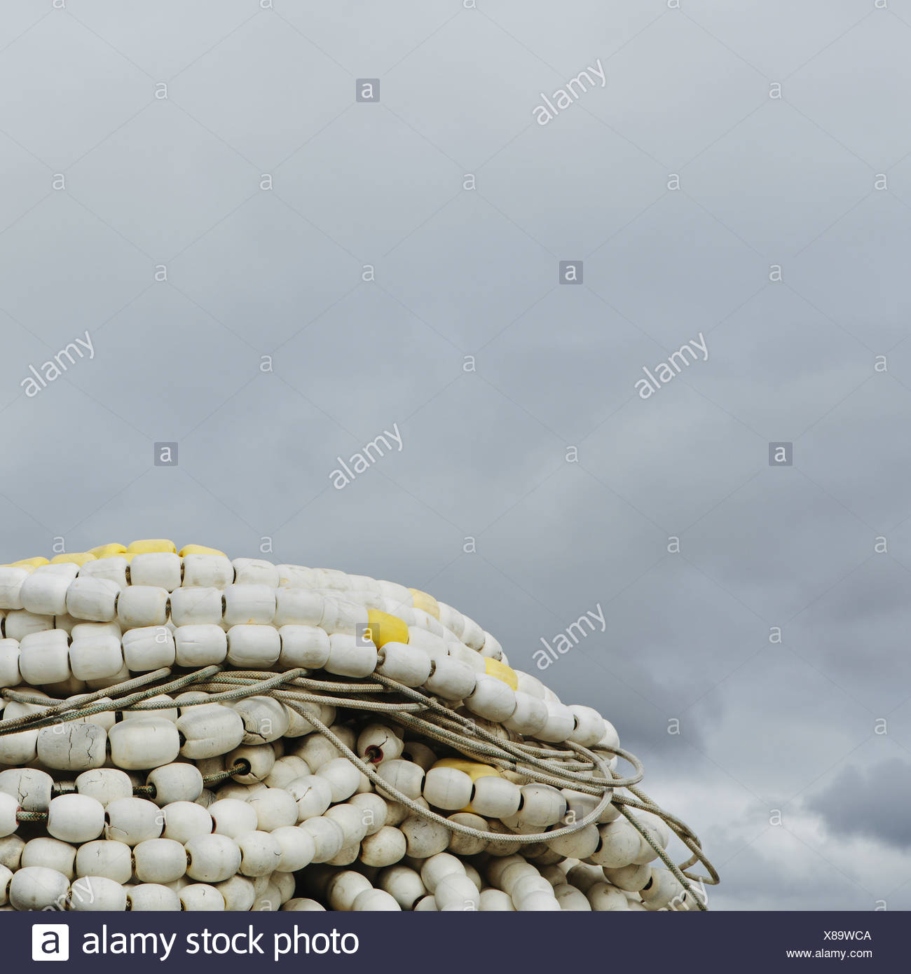Pile of commercial fishing nets with white floats on the quayside at Fisherman's Terminal Seattle - Stock Image