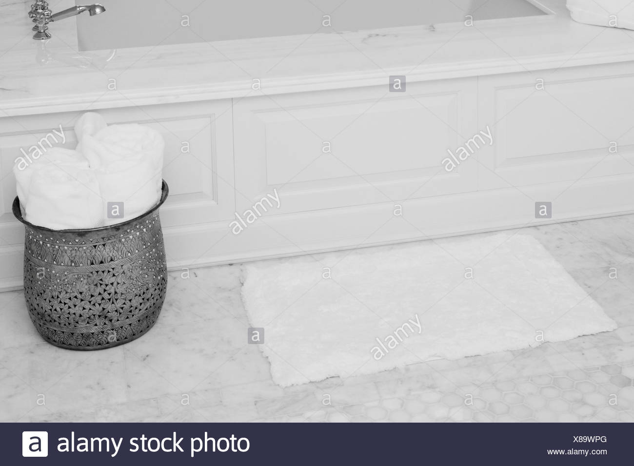 Towels in a container near the bathtub - Stock Image