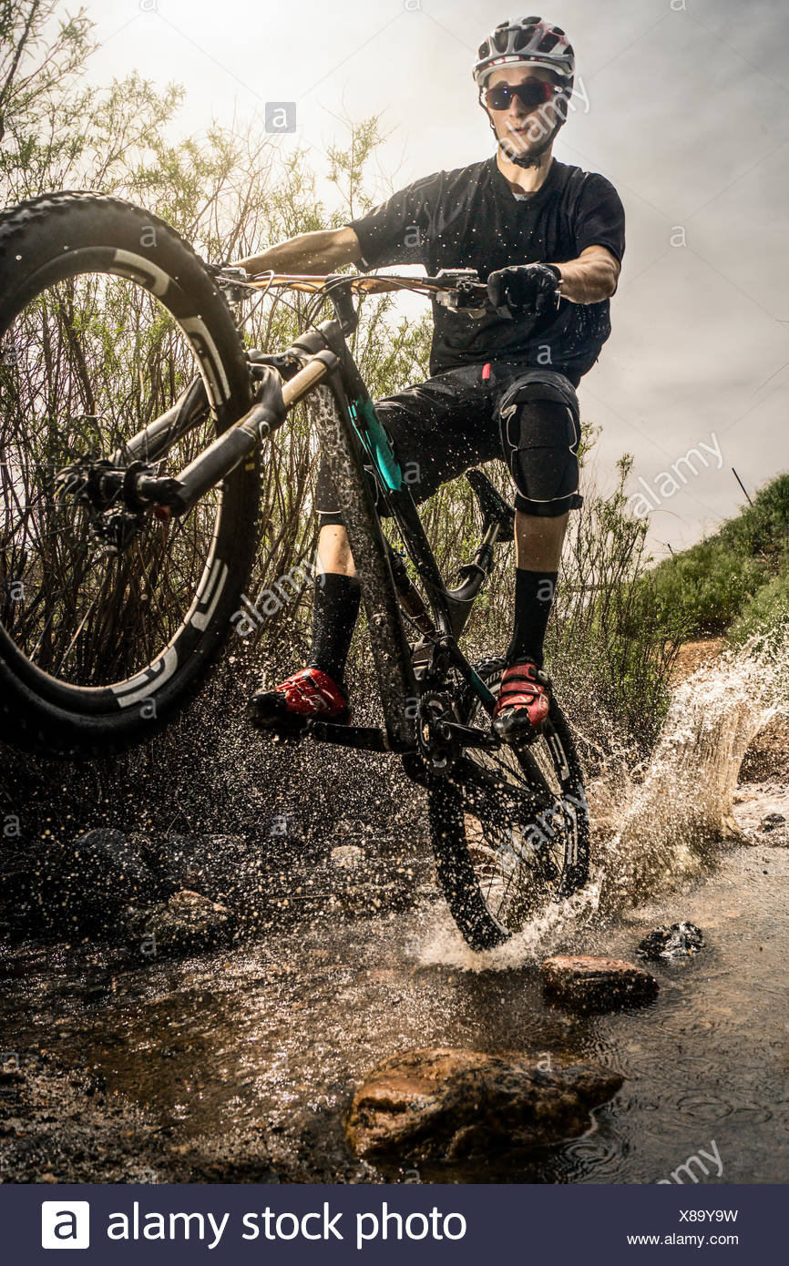 USA, Colorado, Mountain biker riding through stream - Stock Image