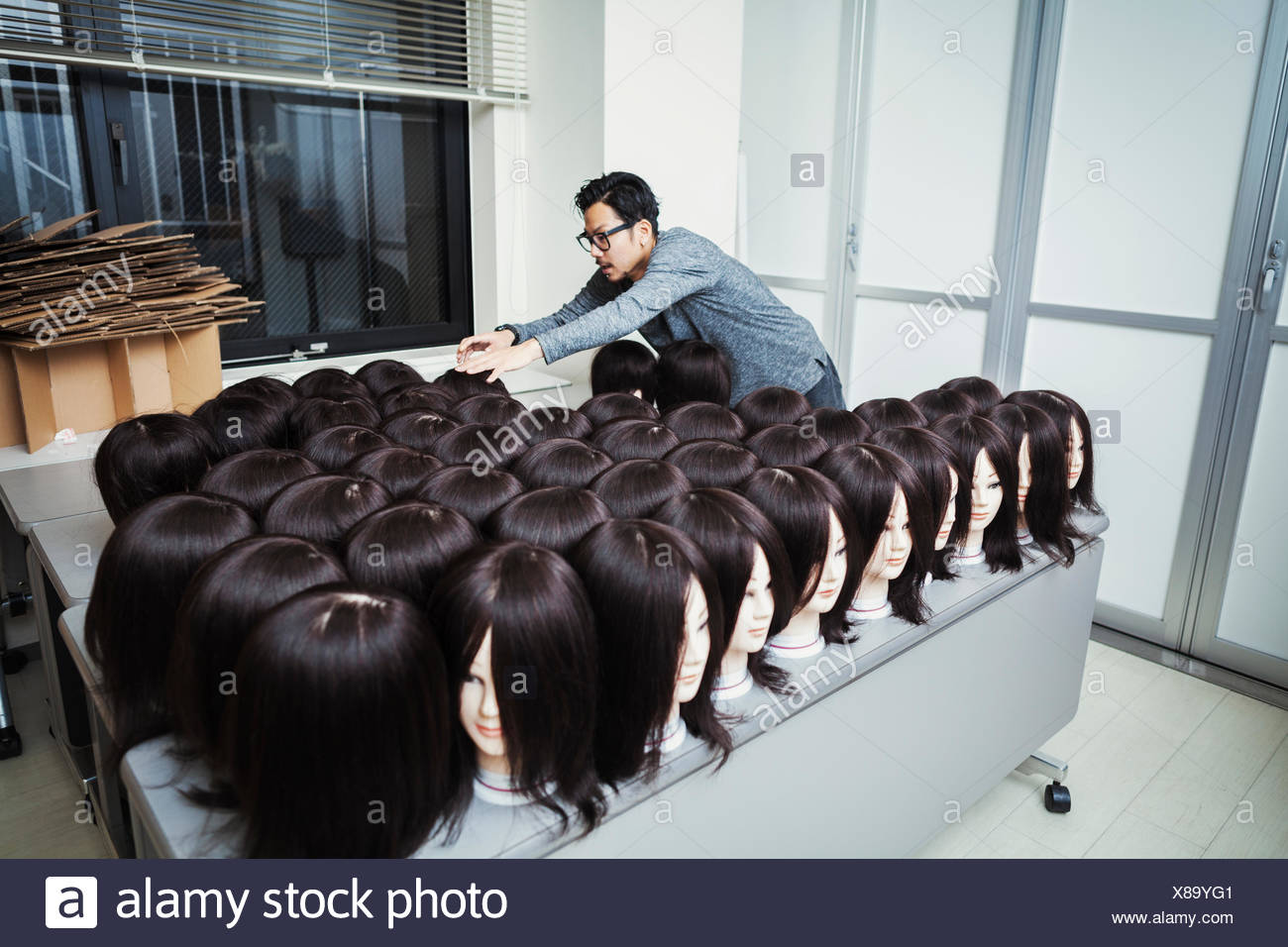 Bearded man wearing glasses standing indoors, arranging mannequin heads with brown wigs. - Stock Image
