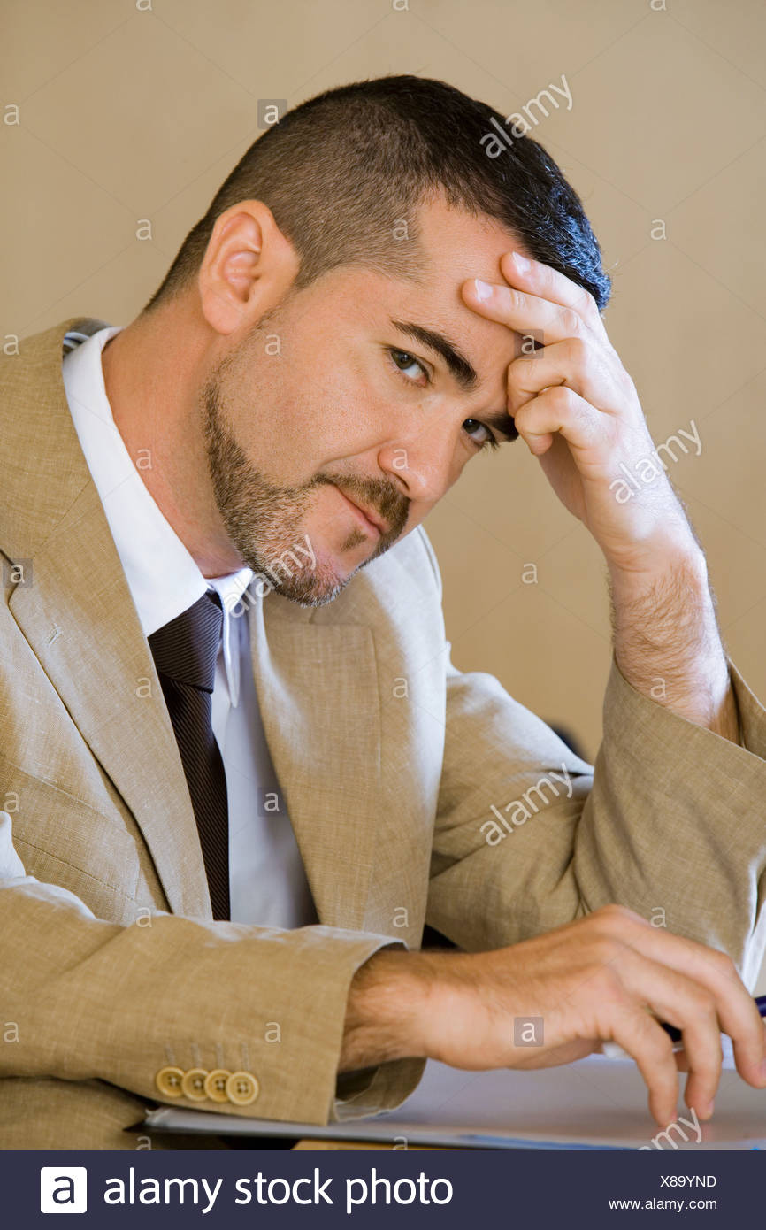 Stressed businessman tapping fingers on desk leaning head on hand side view close up portrait - Stock Image