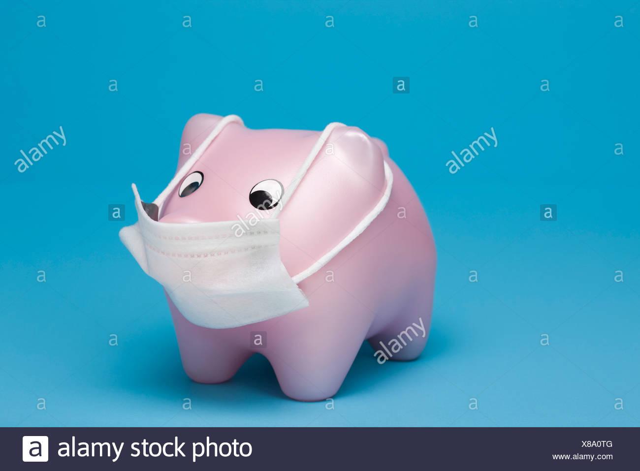 Swine flu concept, toy pig wearing flu mask - Stock Image