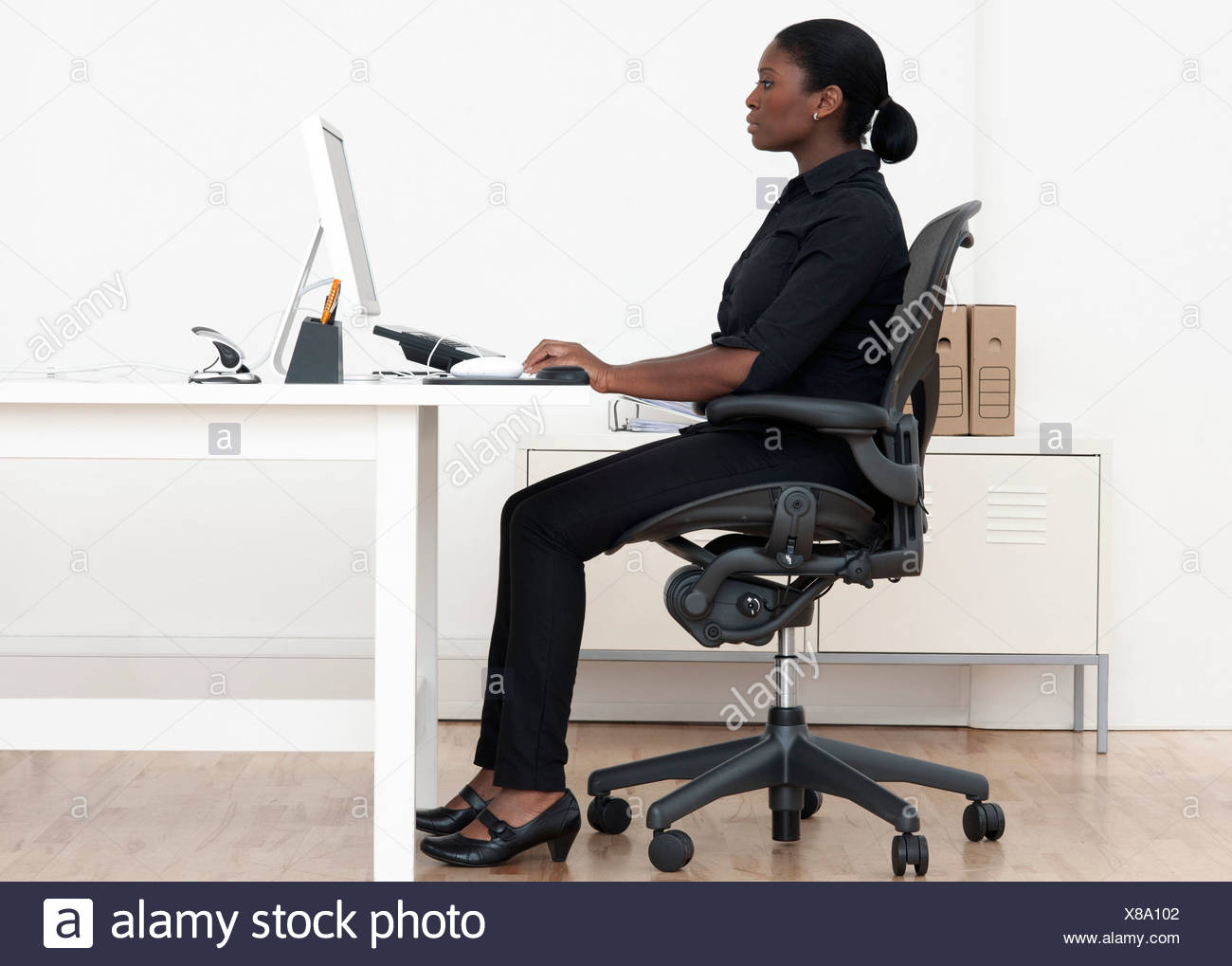 Woman at desk - Stock Image
