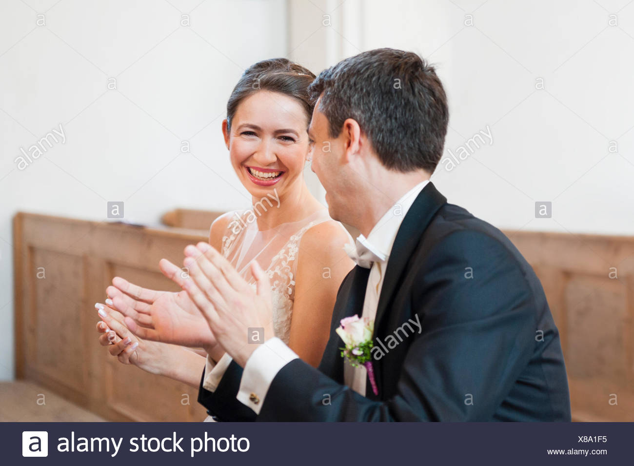 Bride and bridegroom clapping whilst sitting on church pew - Stock Image