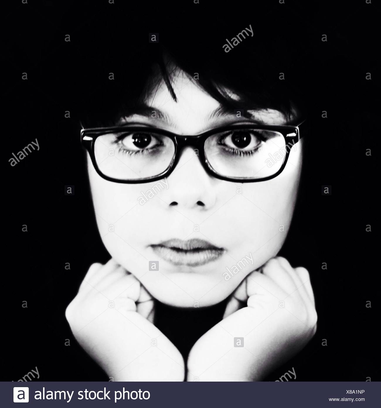 Close-Up Portrait Of Young Woman Wearing Eyeglasses Over Black Background - Stock Image