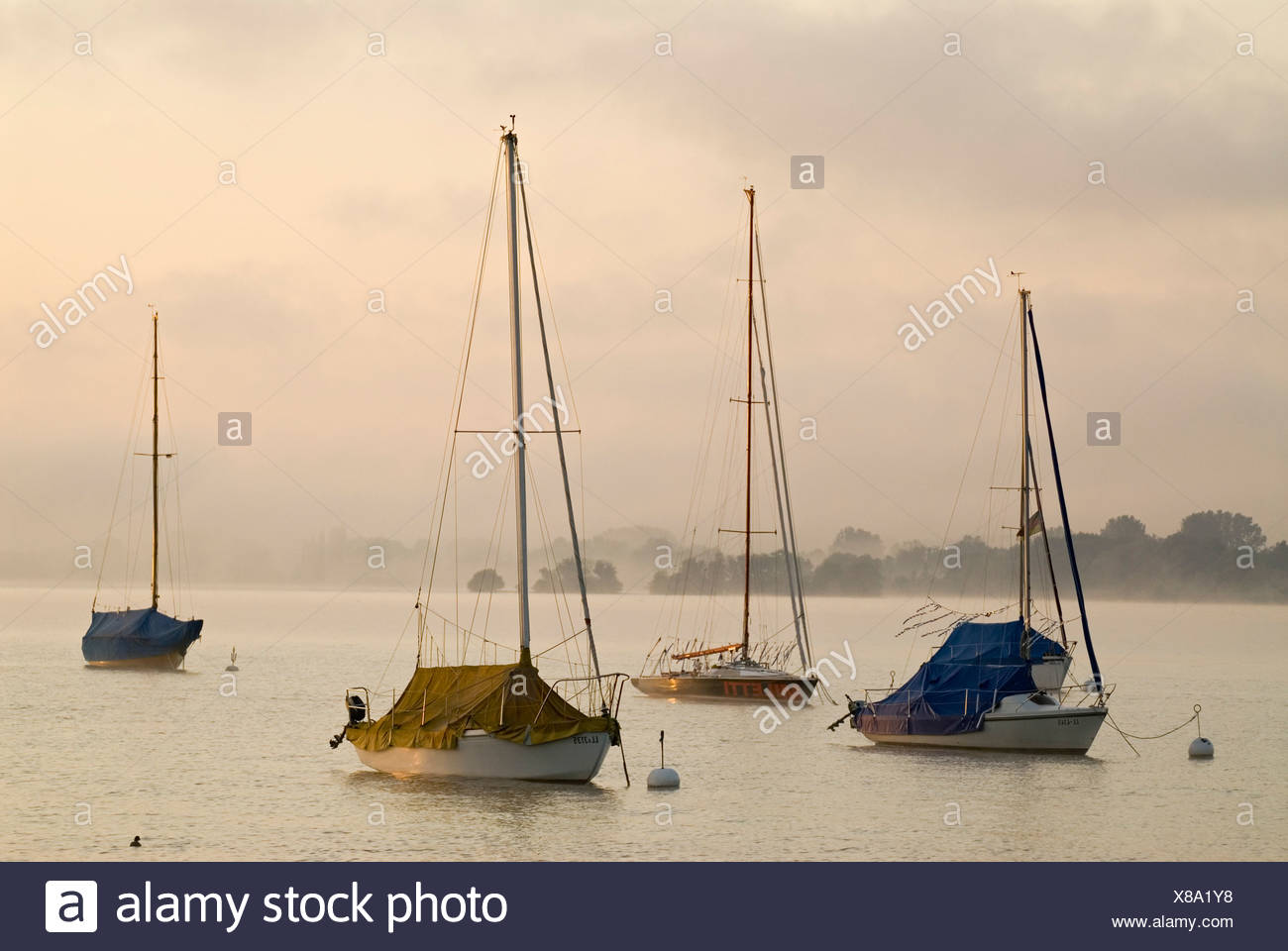 The first light of the day hits sailing boats in front of thick morning fog at Ammersee lake near Schondorf, Bavaria, Germany,  Stock Photo