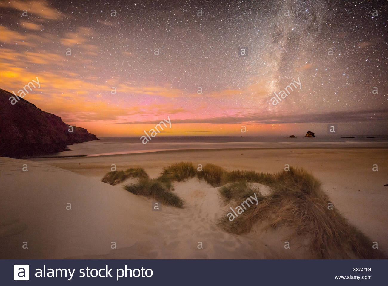 Southern lights, aurora australis with Milky Way above the sea, sand dunes, Sandfly Bay, Dunedin, Otago, Otago Peninsula - Stock Image