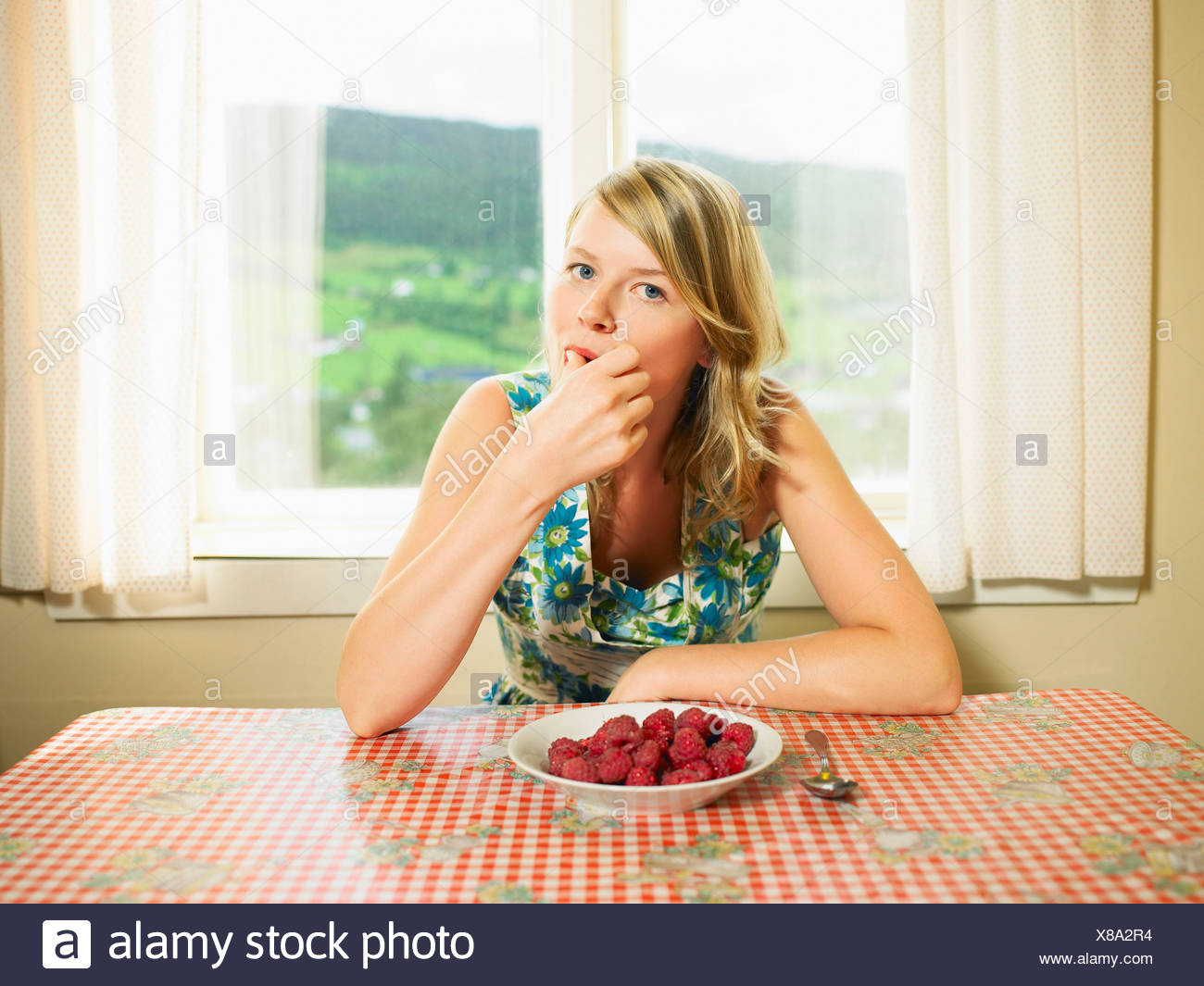 Woman eating bowl of raspberries at table. - Stock Image