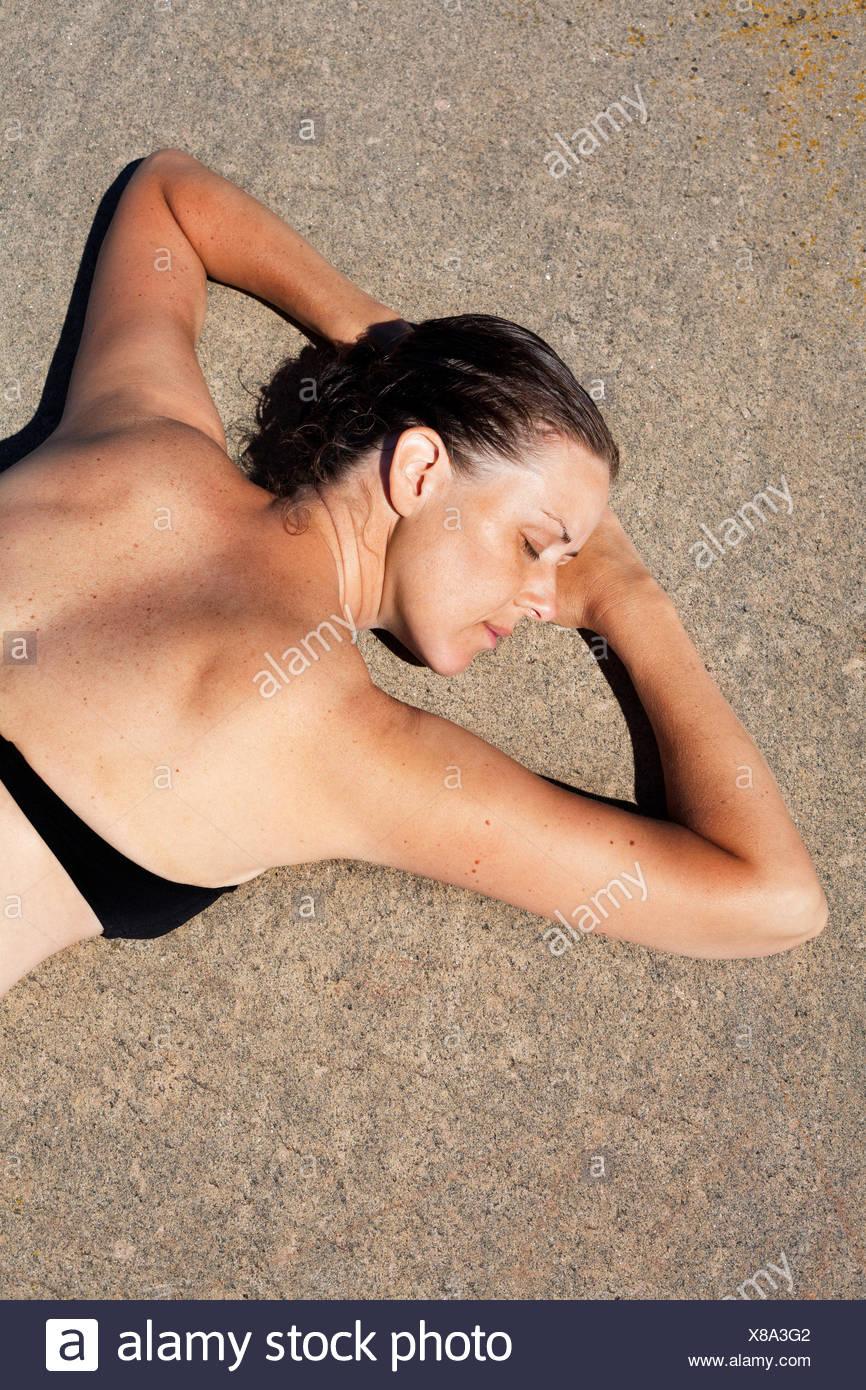 Sweden, Uppland, Runmaro, Barrskar, Elevated view of woman sunbathing - Stock Image