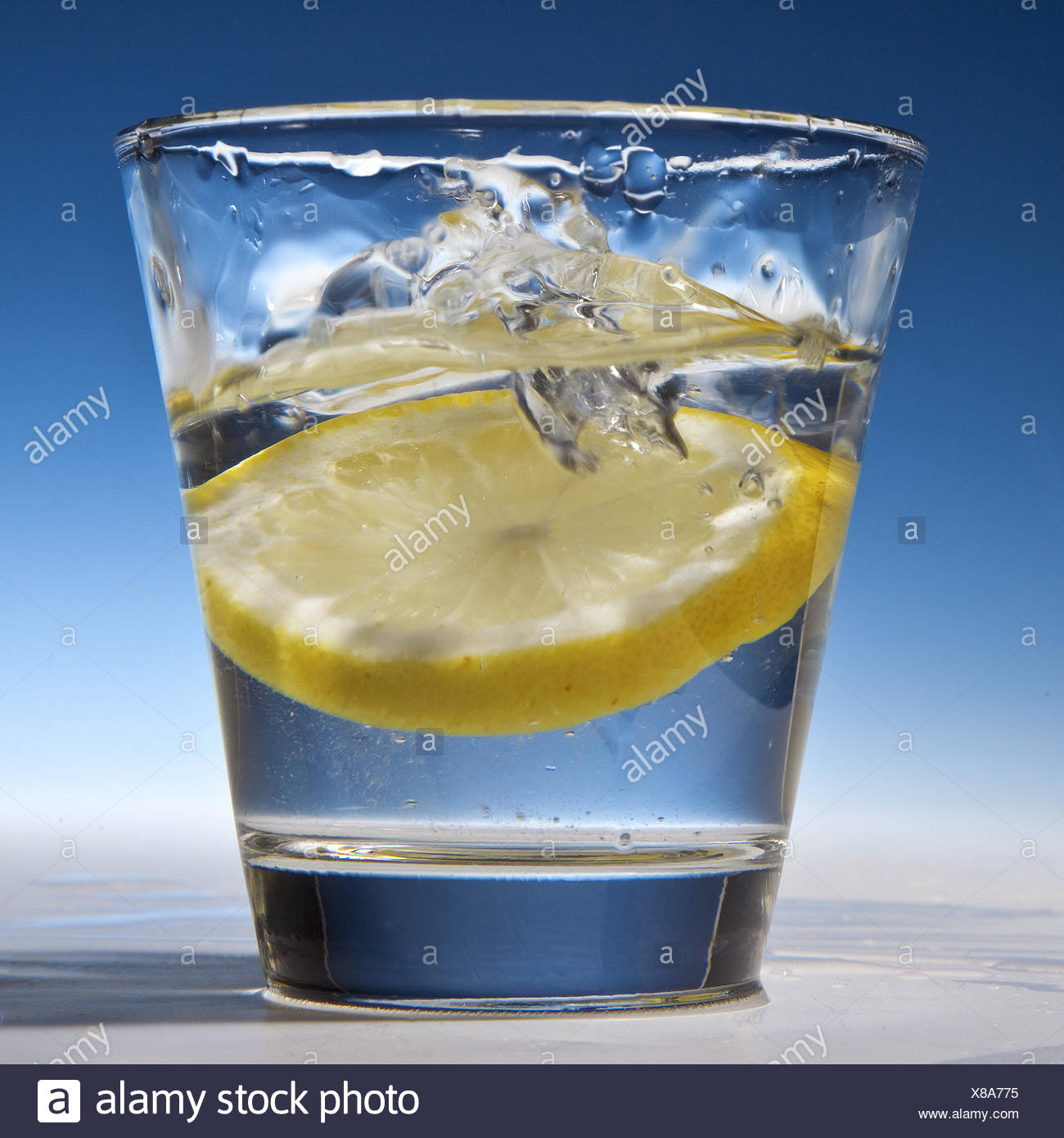 Slice of lemon falling into a glass with water - Stock Image