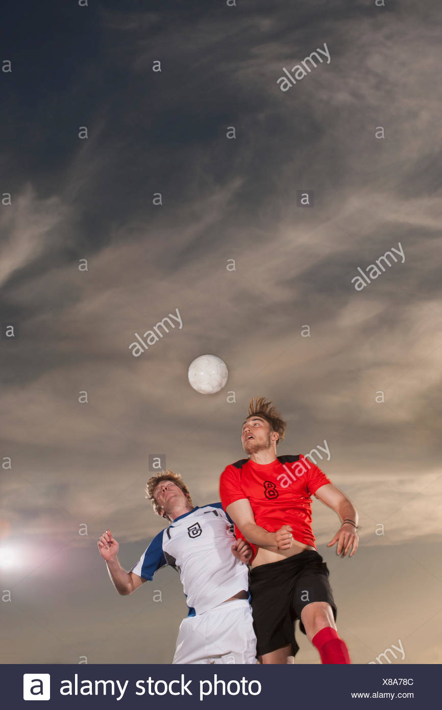 Male soccer players heading ball against sky - Stock Image