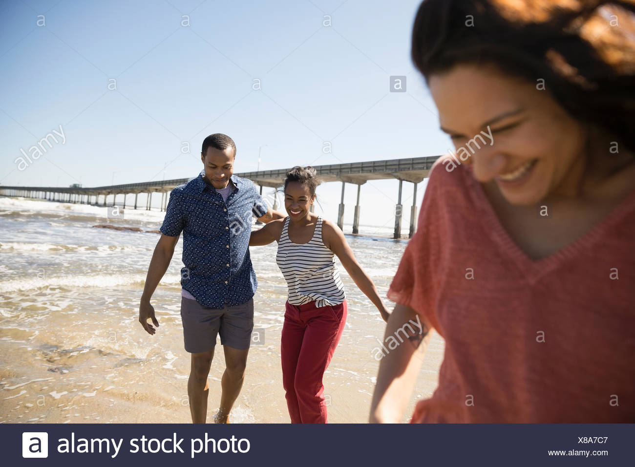 Couple walking on sunny beach - Stock Image