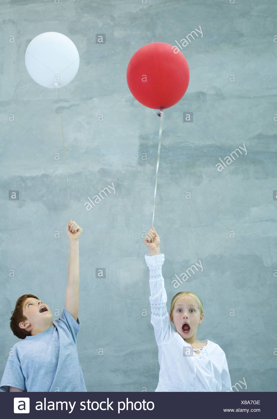 Two children holding balloons, shouting - Stock Image