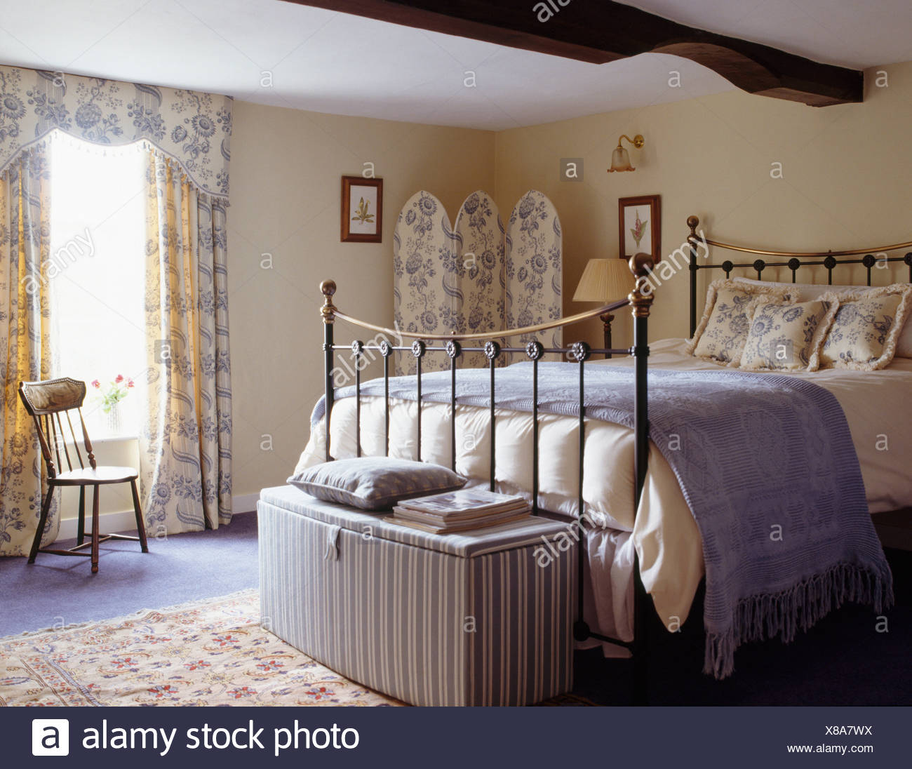 Striped ottoman below brass bed in country bedroom with blue+white ...