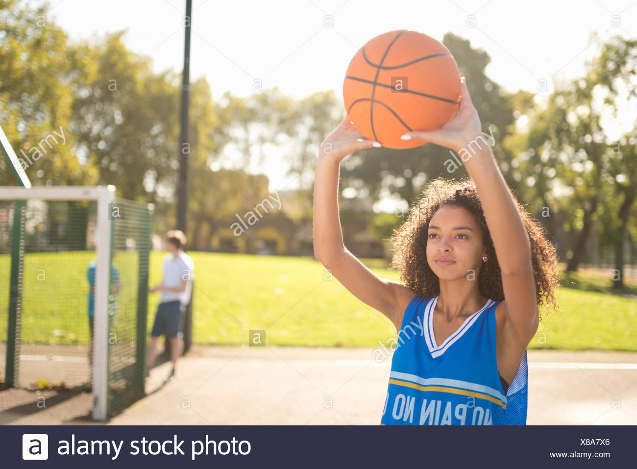 Young female basketball player holding up basketball - Stock Image