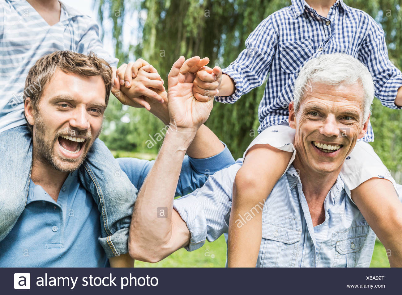 Mid adult man with father giving sons shoulder carry race in garden - Stock Image