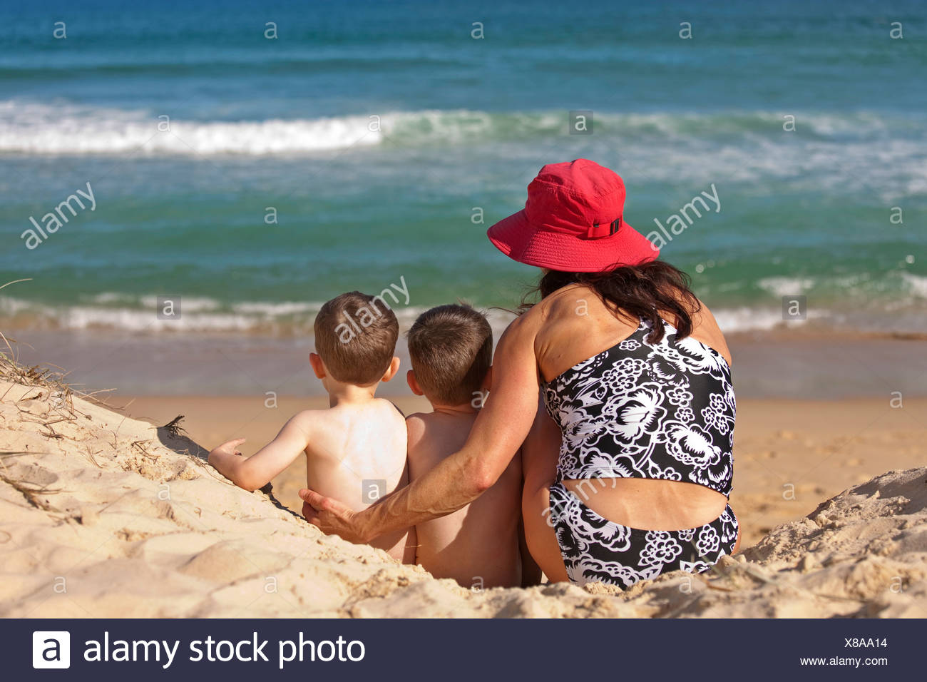 A woman and two children sitting on the sand at Sunshine Beach, Queensland, Australia. - Stock Image