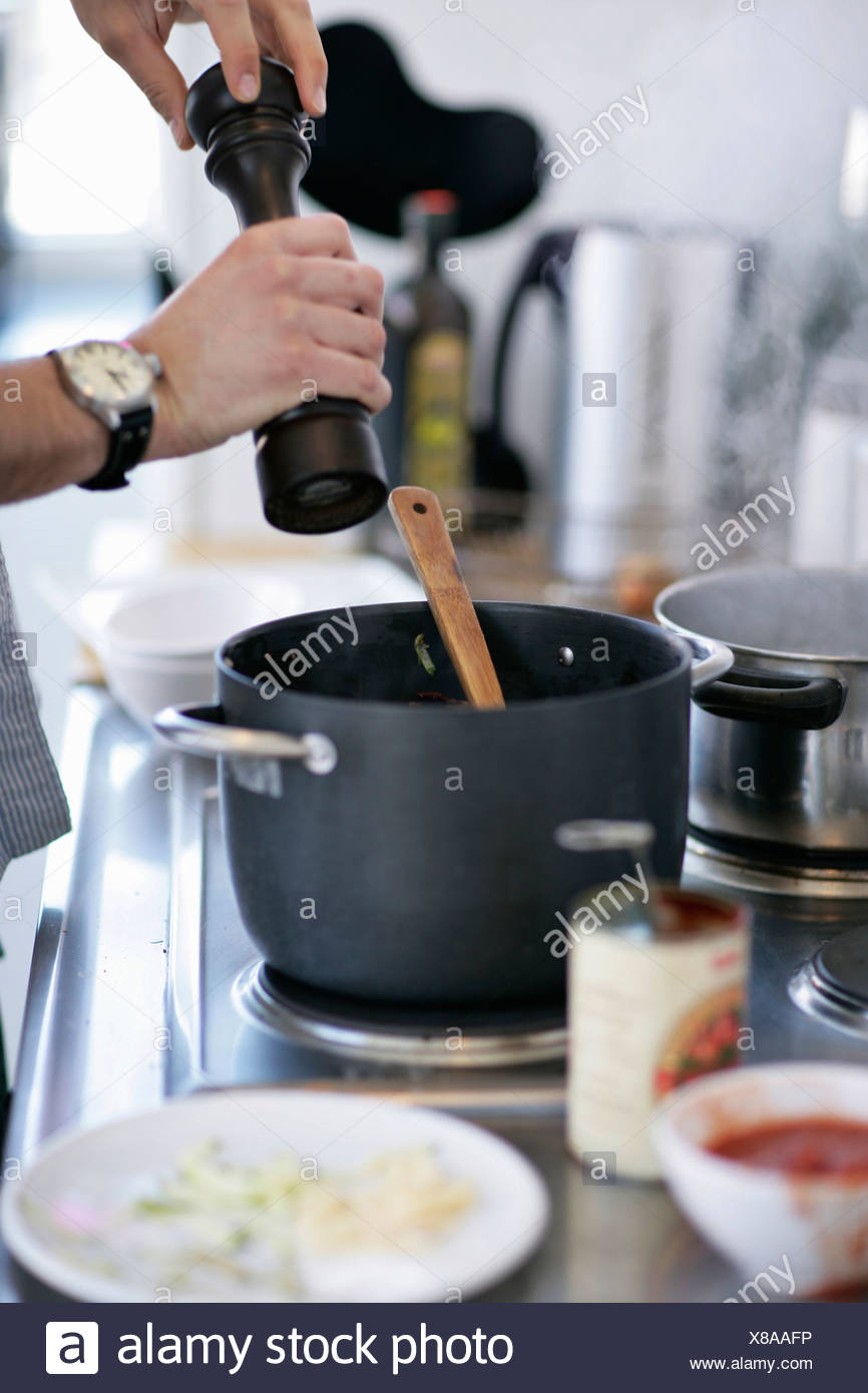 Man grinding pepper into pot - Stock Image