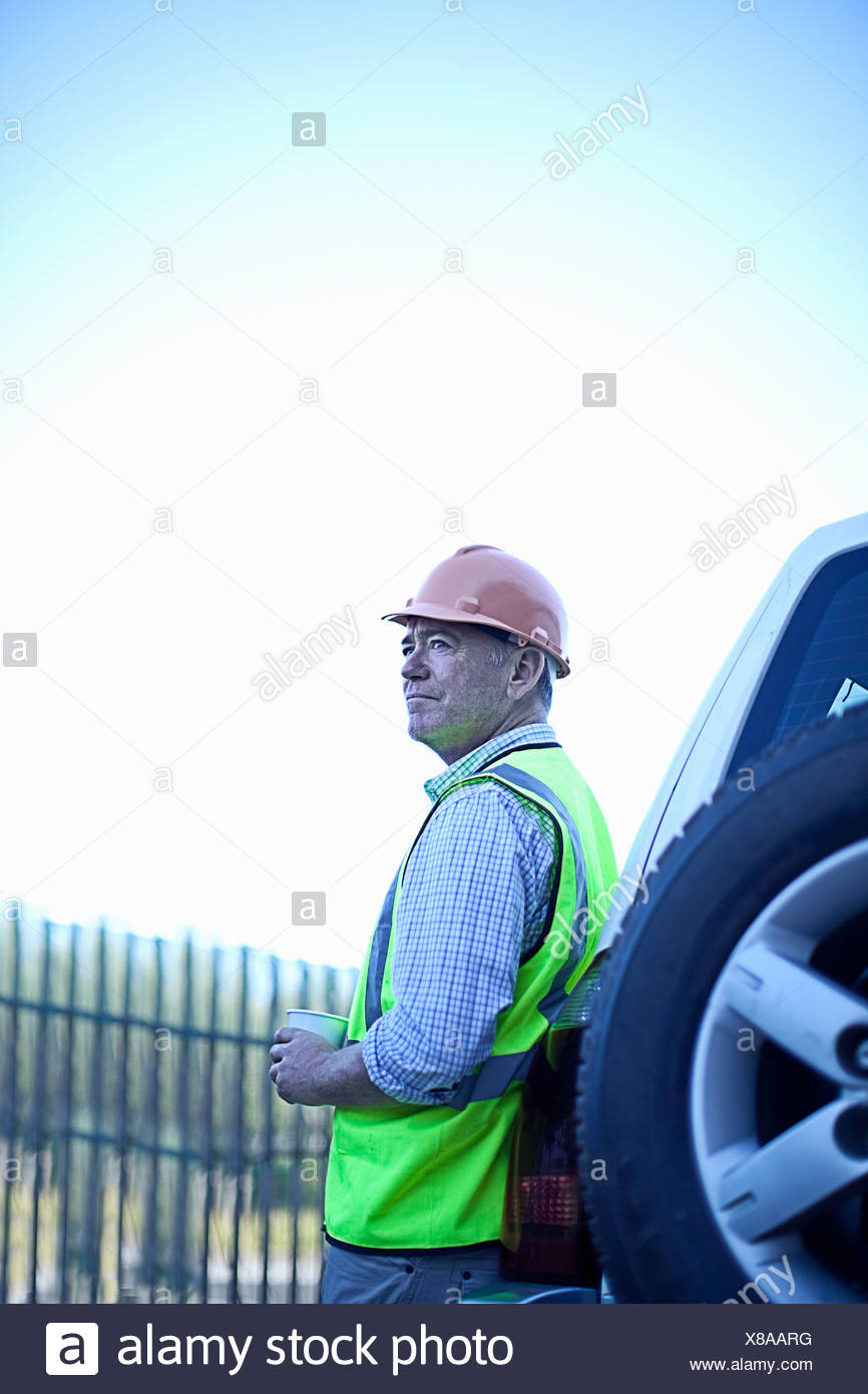 Construction worker leaning on car - Stock Image