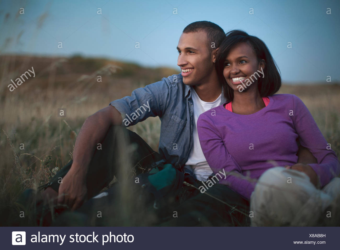 Couple relaxing in field together at dusk. - Stock Image