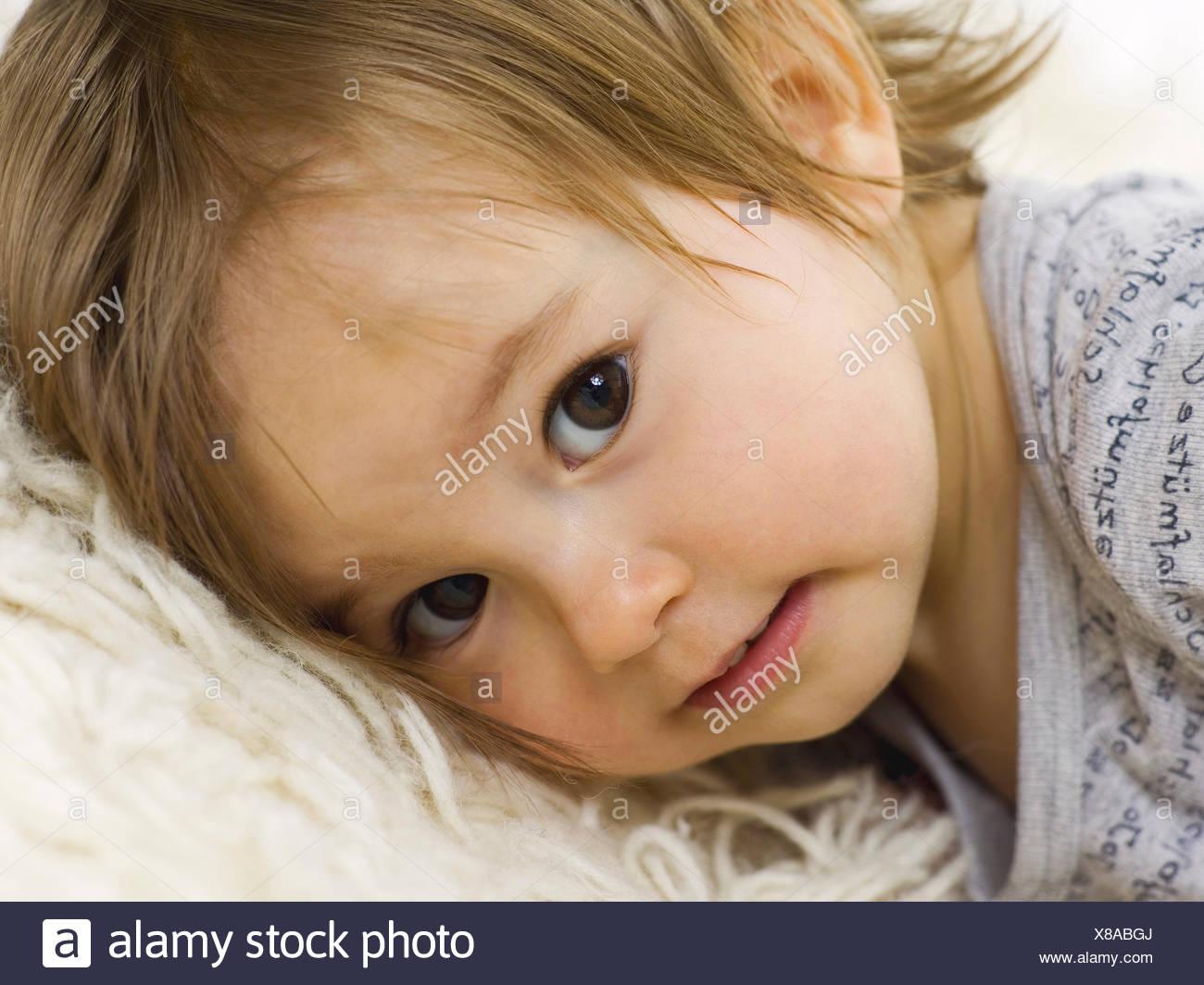 toddler,lying,cuddle - Stock Image
