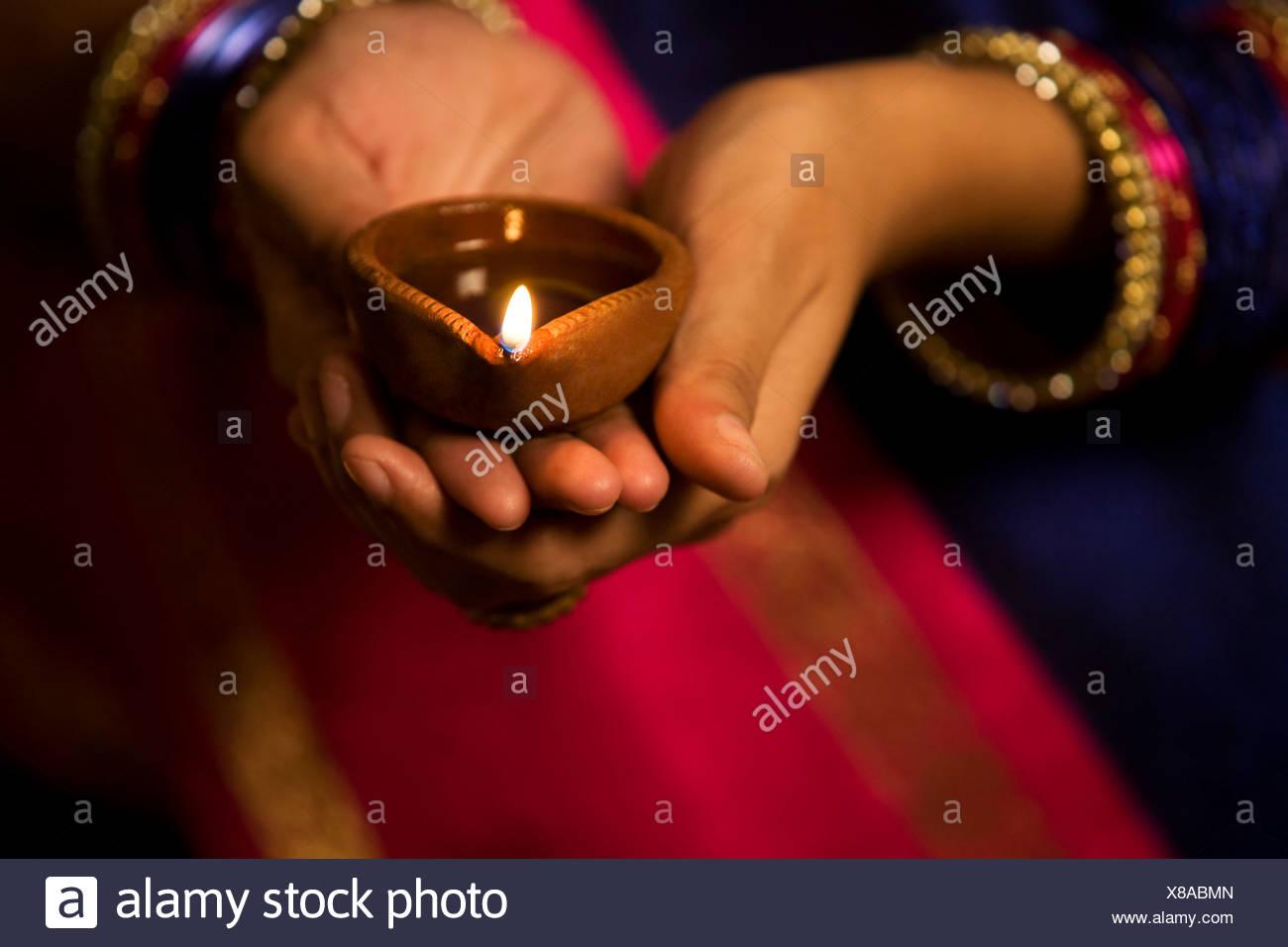 Woman holding a diya - Stock Image
