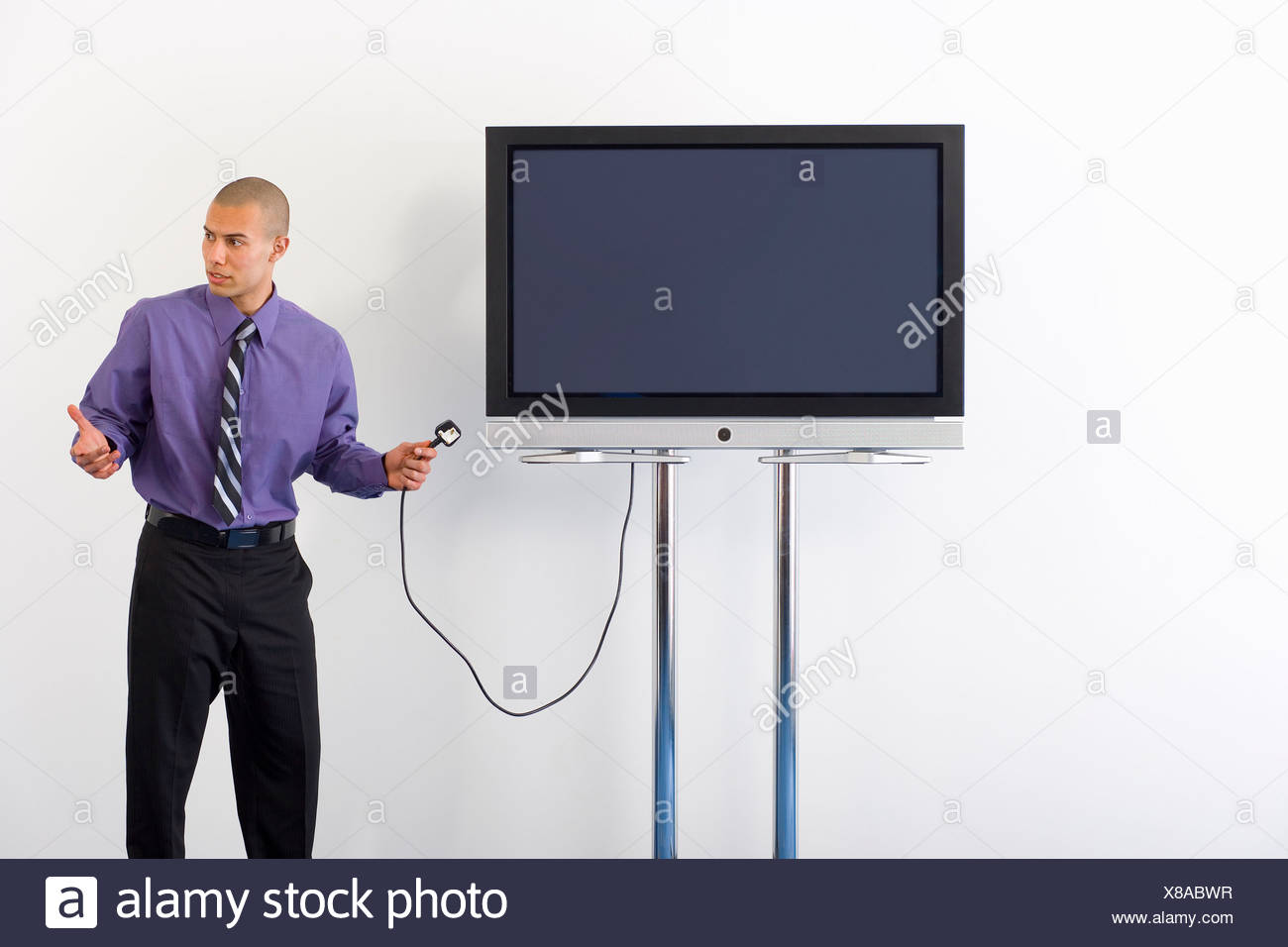 Businessman holding plug to widescreen television in boardroom, shrugging shoulders, looking away - Stock Image