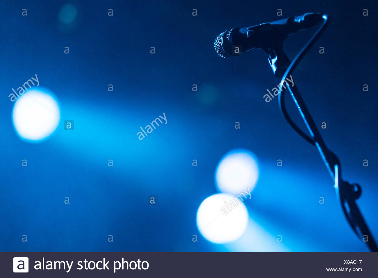 Microphone on a stand in the spotlight - Stock Image