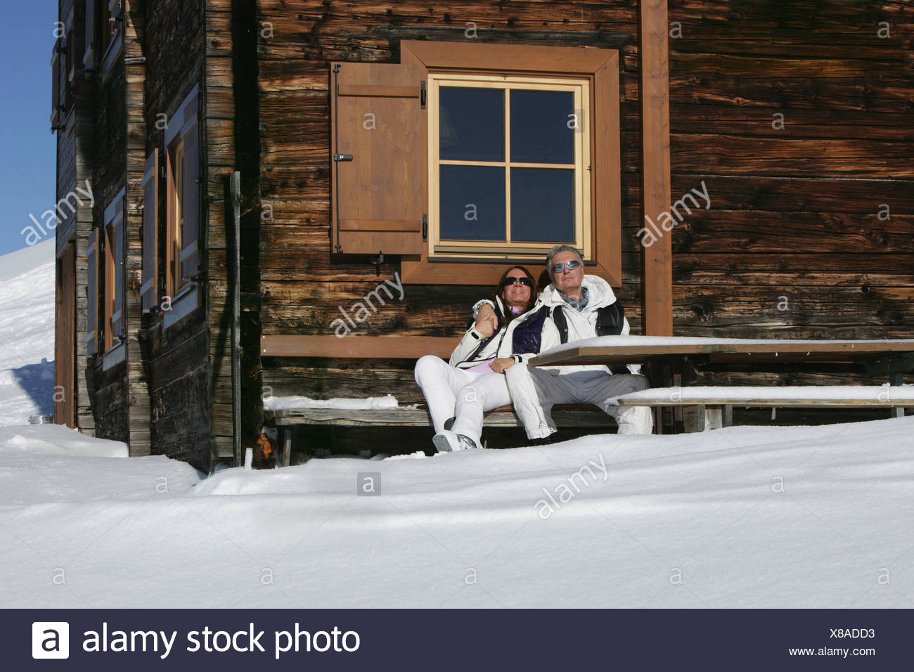 Couple relaxing outdoors at ski chalet - Stock Image