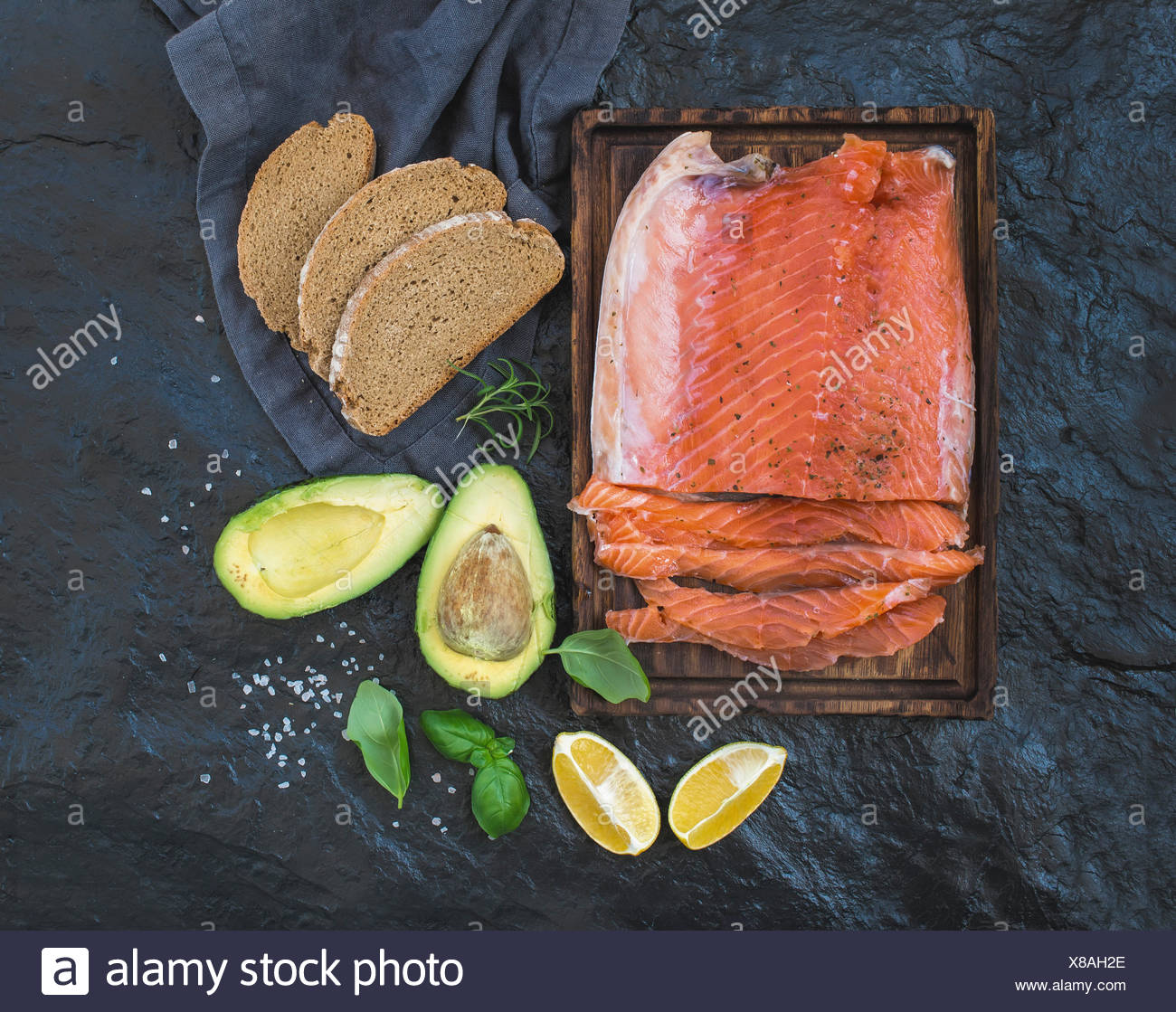 Smoked salmon filet with lemon, avocado, fresh herbs and bred on wooden serving board over dark stone backdrop, top view - Stock Image