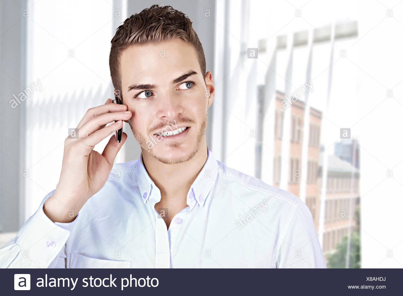 Portrait of a beautiful young man with handy - Stock Image