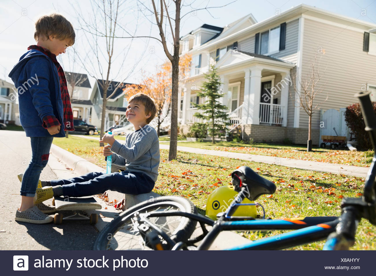 Brothers with bike and sidewalk at neighborhood curb - Stock Image