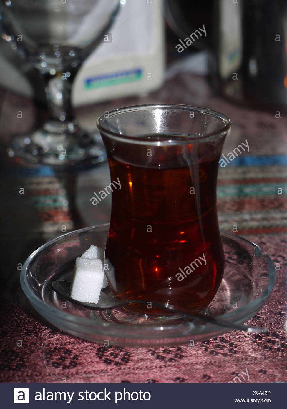 A glass of strong Turkish tea with lumps of sugar - Stock Image