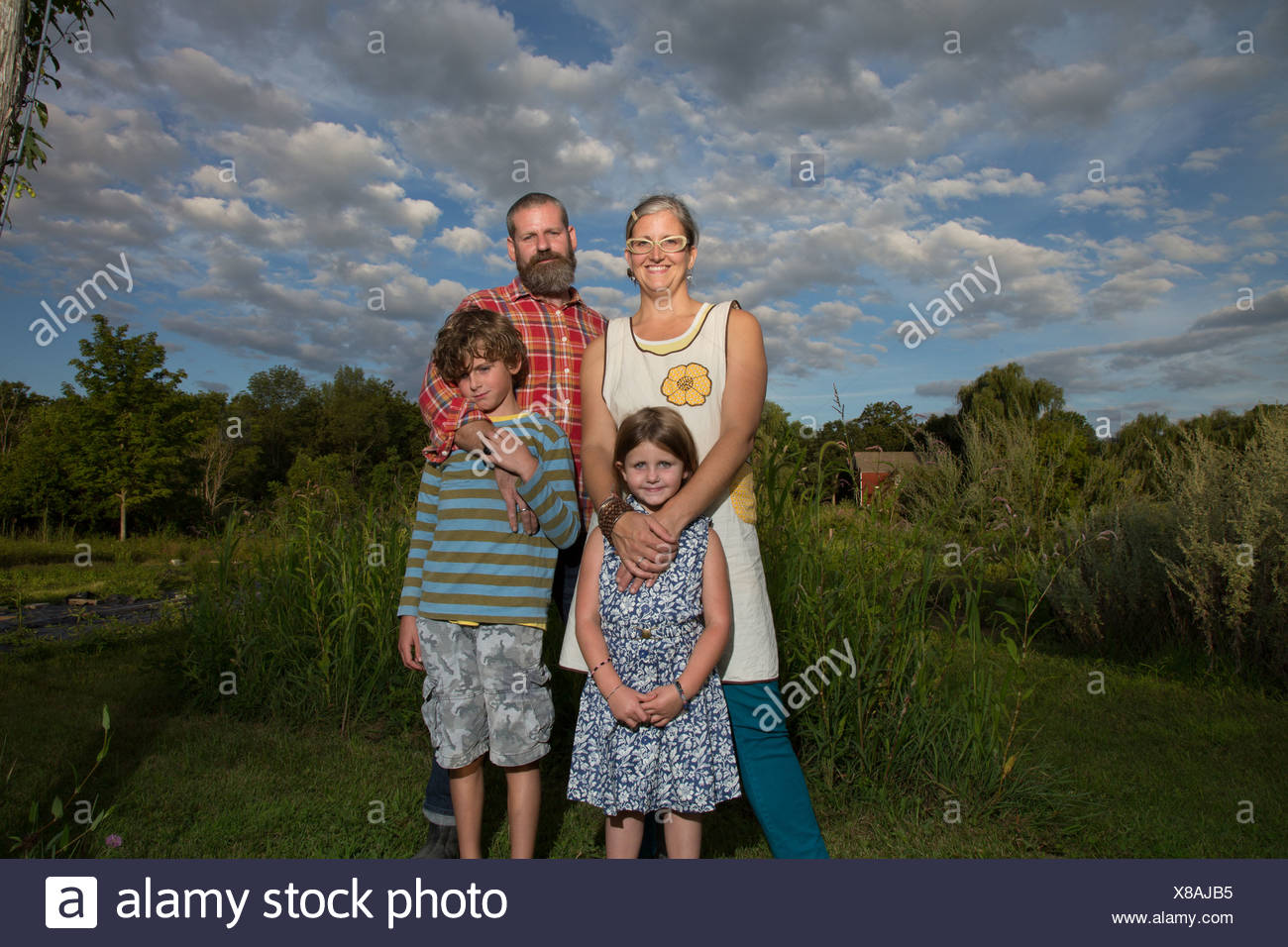 Portrait of couple with children on family herb farm - Stock Image