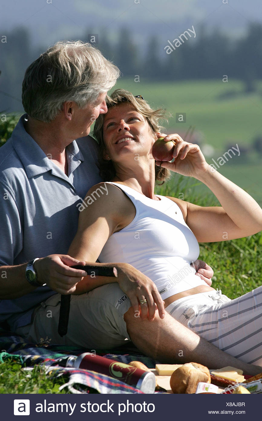 Couple middle age old person relax outside picnic food nature excursion hiking Hemberg Toggenburg canton St - Stock Image